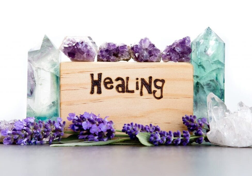 Healing - word burnt in wood with purple lavender flowers, amethyst, fluorite and quartz crystals on gray / grey slate with white background